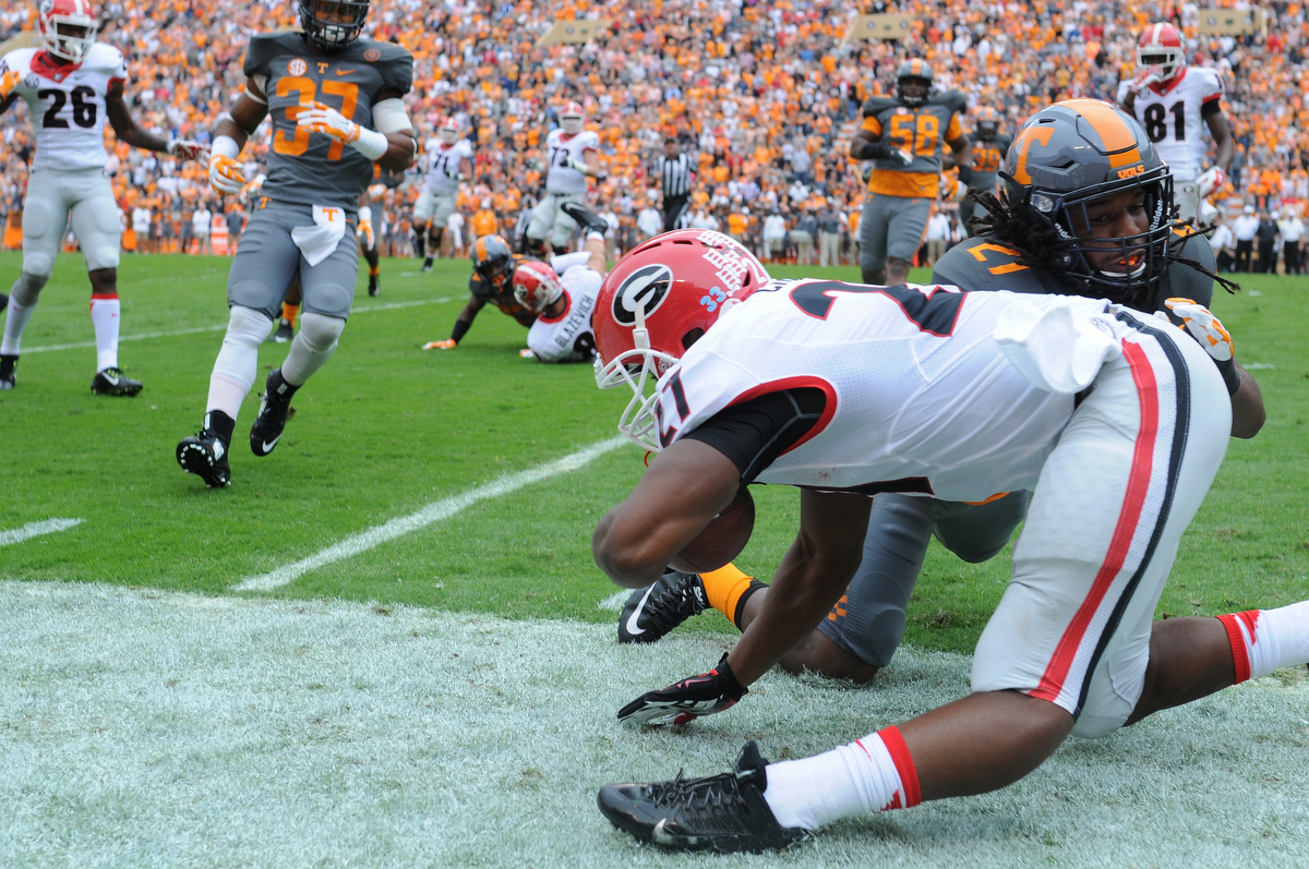 Georgia running back Nick Chubb (27) is injured after being pushed out of bouns by Tennessee linebacker Jalen Reeves-Maybin (21) during the first half of an NCAA college football game between Georgia and Tennessee on Saturday, Oct. 10, 2015, in Knoxville, Tenn. (AJ Reynolds/Staff, @ajreynoldsphoto)