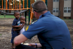 Athens-Clarke County Police Officer Lee Crosby talks with a group of children near the playground at Bethel Midtown Village on Thursday, July 23, 2015 in Athens, Ga. The Athens-Clarke County Police Department has seen a decrease in crime since instituting a community oriented policing approach at Bethel. (AJ Reynolds/Staff, @ajreynoldsphoto)