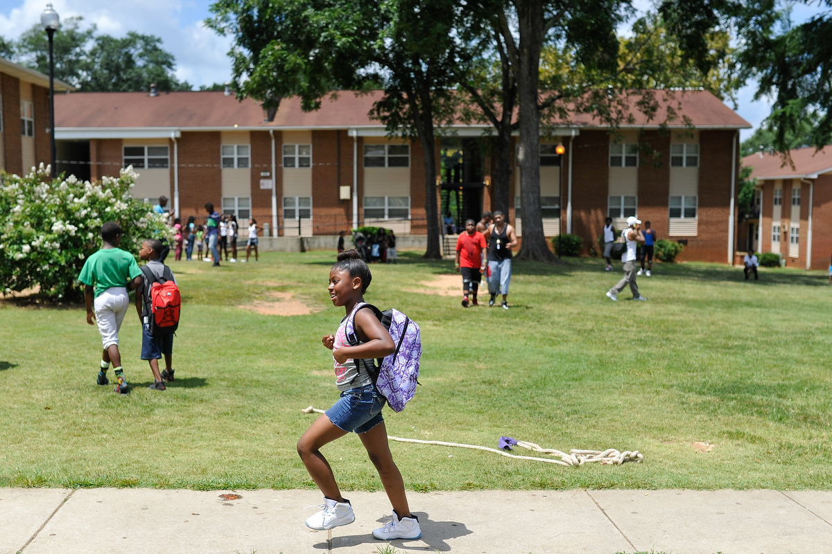 A young girl walks with a new backpack before the start of the school year at Bethel Midtown Village on Saturday, Aug. 8, 2015 in Athens, Ga. (AJ Reynolds/Staff, @ajreynoldsphoto)