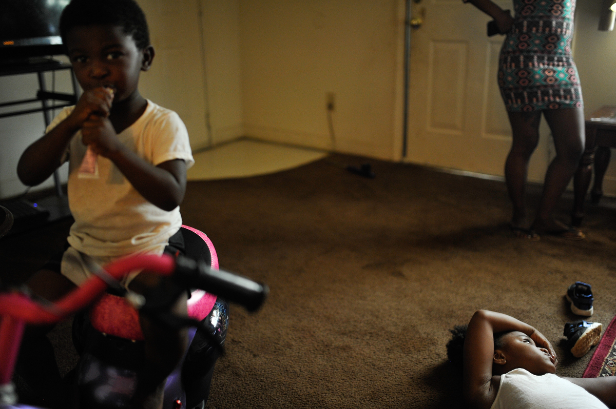 Daryl Nottingham, left, eats a snack while Da'Nasija Brown  lays on the floor of her mother's apartment at Bethel Midtown Village on Wednesday, July 15, 2015 in Athens, Ga. (AJ Reynolds/Staff, @ajreynoldsphoto)