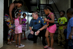 Athens-Clarke County Police Officer Lee Crosby talks with  group of children and parents in one of the breezeways at Bethel Midtown Village on Thursday, July 23, 2015 in Athens, Ga. Crosby brings stickers to give to the children and focuses on community oriented policing. (AJ Reynolds/Staff, @ajreynoldsphoto)