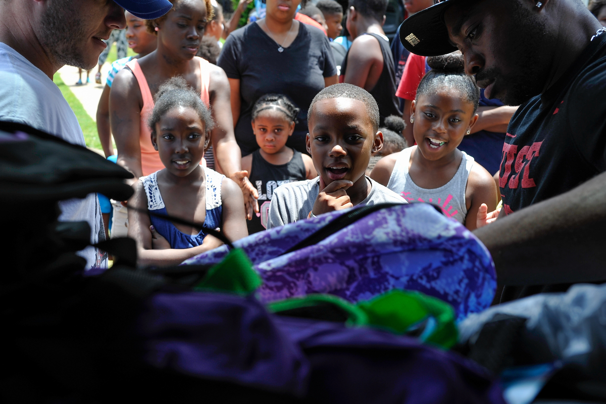 Children gather around the back of a car to receive backpacks provided by the Classic City Father's Foundation and the University of Georgia during the back to school party at Bethel Midtown Village on Saturday, Aug. 8, 2015 in Athens, Ga. (AJ Reynolds/Staff, @ajreynoldsphoto)