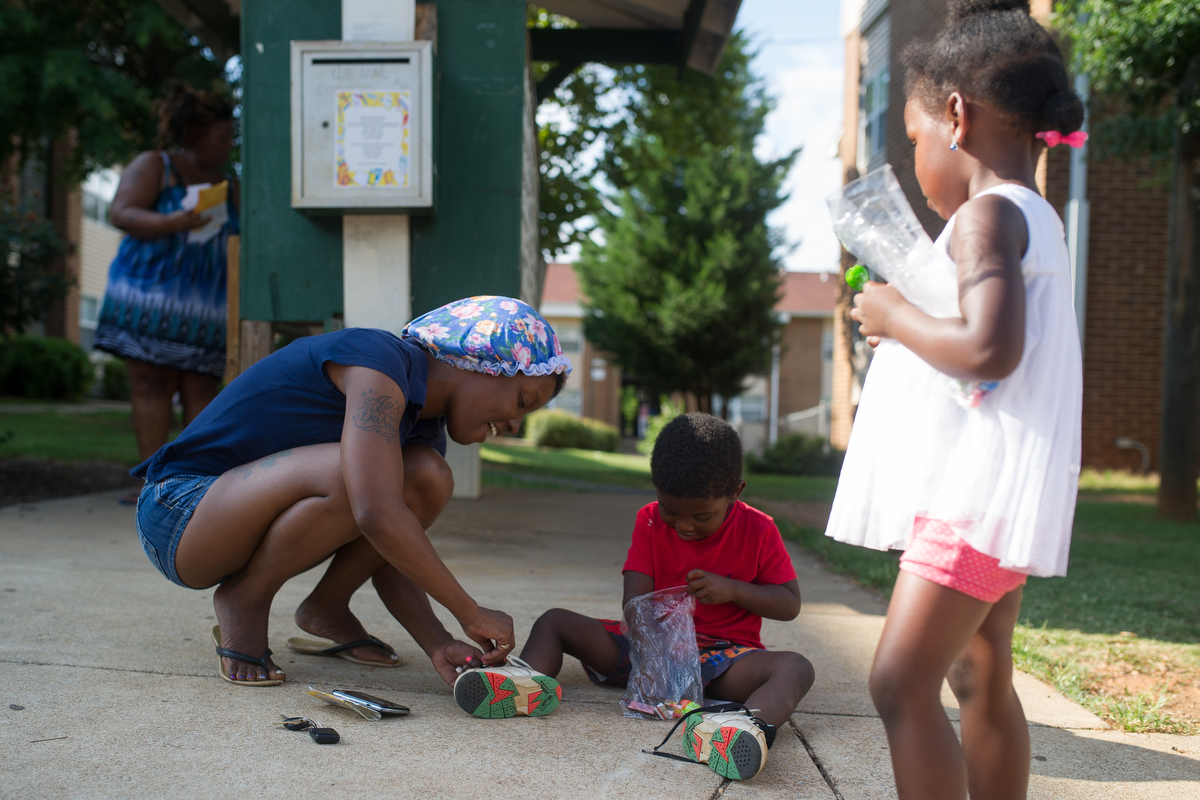 Shawn Burgess, left, ties her son, Daryl Nottingham's shoe after Nottingham returned from a birthday party at Bethel Midtown Village on Friday, July 24, 2015 in Athens, Ga. (AJ Reynolds/Staff, @ajreynoldsphoto)
