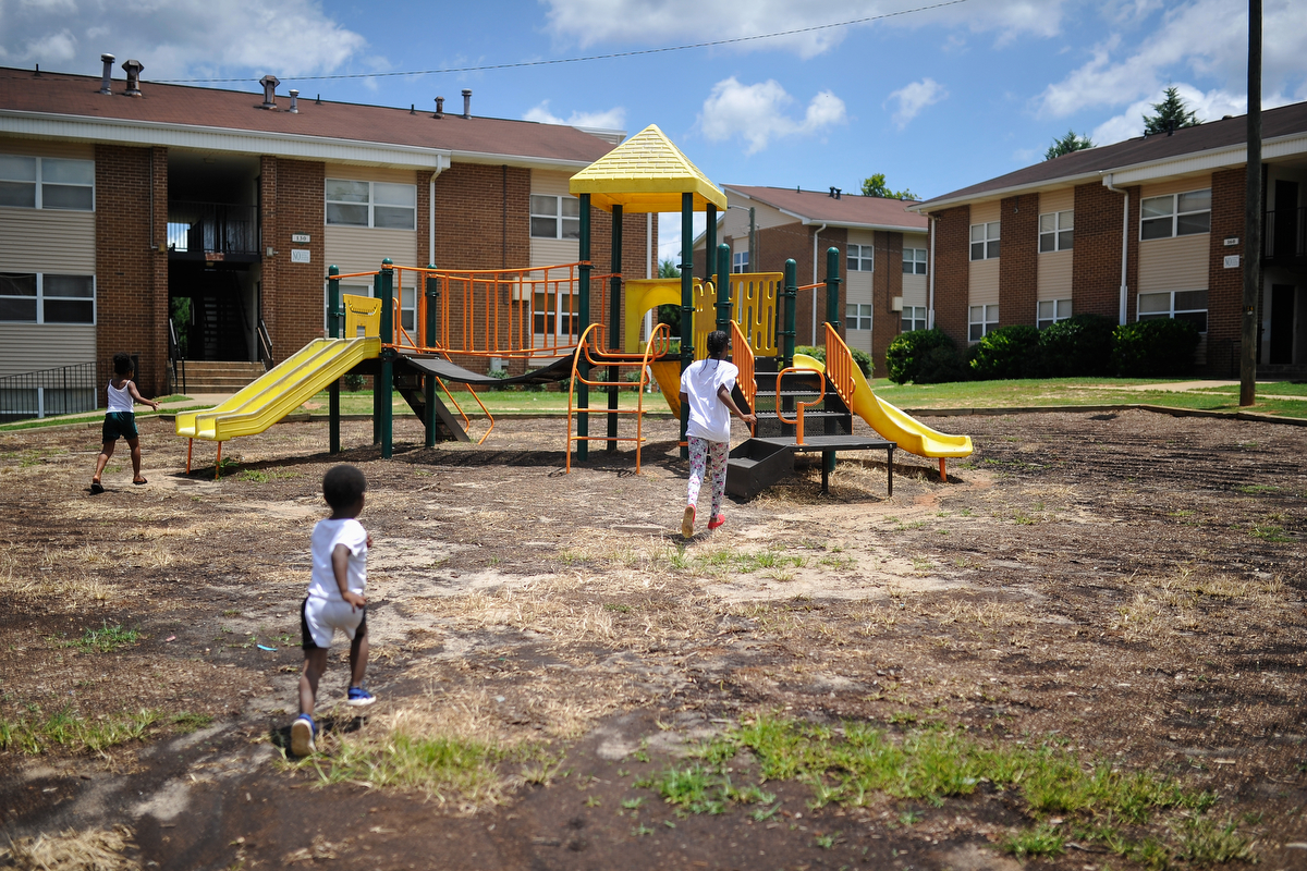 Da'Nasija Brown, from left, Daryl Nottingham and Ja'Niya Burgess run toward a playground set at Bethel Midtown Village on Wednesday, July 15, 2015 in Athens, Ga. (AJ Reynolds/Staff, @ajreynoldsphoto)