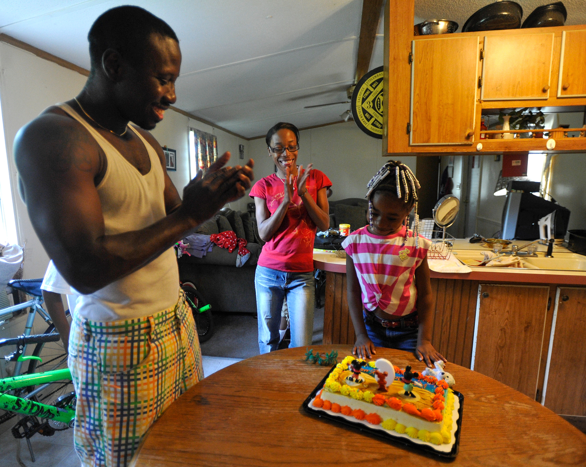 Katima Hall looks down at her birthday cake during her sixth birthday party while her mother Kim Baughns on Thursday, September 4, 2014, in Athens, Ga. (AJ Reynolds/Staff, @ajreynoldsphoto)
