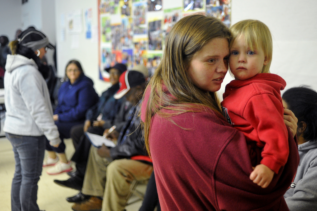 Amber Seay holds her daughter Kaylie Street while waiting in line during a food distribution drive at Joy Baptist Church on Tuesday, Nov. 18, 2014, in Hull, Ga. Seay, pregnant with her second child said of the chuch, {quote}Food stamps don't get us through the entire month, so if it wasn't for this place, we'd starve.{quote} (AJ Reynolds/Staff, @ajreynoldsphoto)