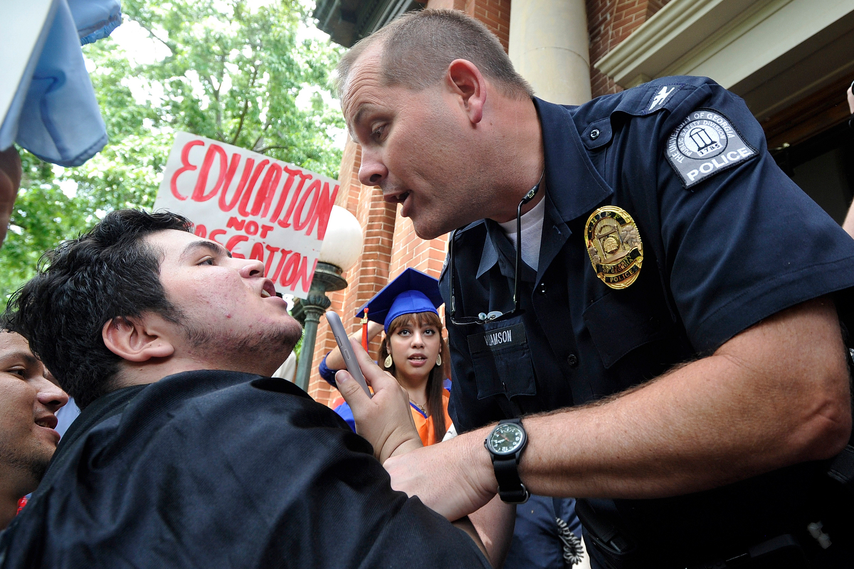 Police Chief Jimmy Williamson asks Alejandro Galeana Salinas and other protestors to clear the steps to the Administration Building on the UGA campus as a group protests a 2010 State Board of Regents policy that keeps undocumented immigrants out of several Georgia colleges on Monday, April 28, 2014, in Athens, Ga. (AJ Reynolds/Athens Banner-Herald)