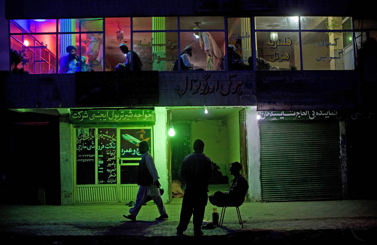 Men staying at a guest house in Kabul, Afghanistan pray together on the first floor as the door man negotiates with customers on the street on March 25, 2010. The neighborhood surrounding Chamana Huzari stadium was once decimated by Afghanistan's civil war before the Taliban came to power.
