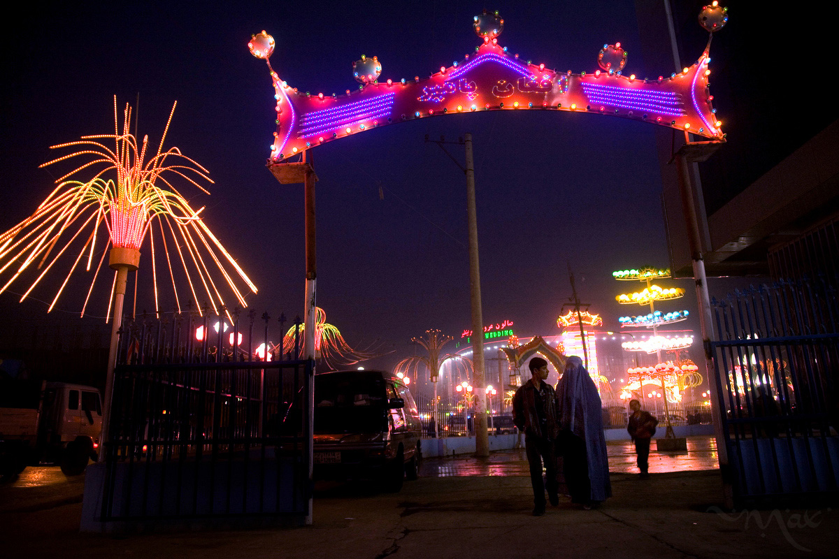 A couple walks under the sign of a wedding hall in Kabul, Afghanistan on Monday, October 5, 2007. Wedding halls attempt to out do each other with lights to attract more customers in the competitive wedding hall market. Young men are facing more cultural pressure as the cost they and their families are expected to pay for a wedding rises. Guest lists in the hundreds and a whole series of parties for the wedding process push some weddings to over $20,000.