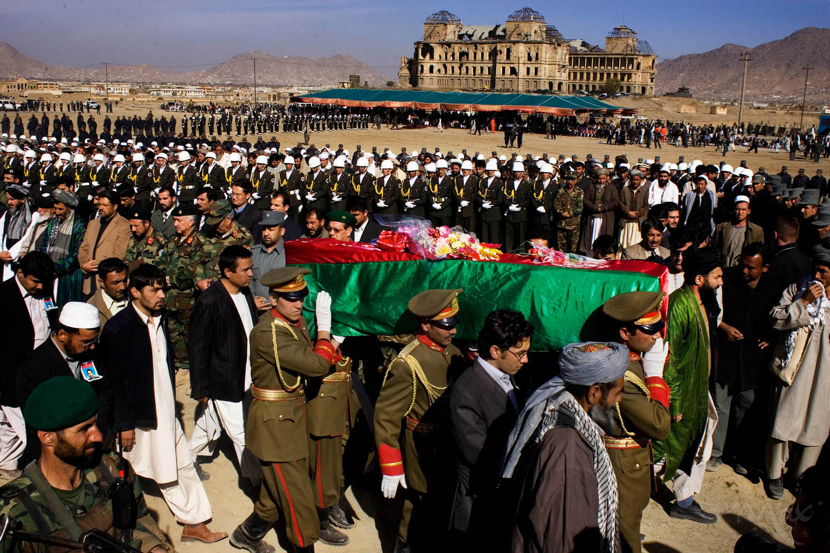 Rows of Afghan dignitaries, military, police and mourners pay last respects to six parliamentarians including opposition leader Mustafa Kazimi, during a state funeral near the Darulaman Palace, in background, in Kabul, Afghanistan on Thursday November 8, 2007. The lawmakers and six of their bodyguards, who were also killed in the attack, were buried together in a place of honor near the location of a planned new parliament building. Thousands attended the official ceremony during the second of three national days of mourning for the 52 killed in a suicide attack in Baghlan province on Tuesday, November 6, 2007.