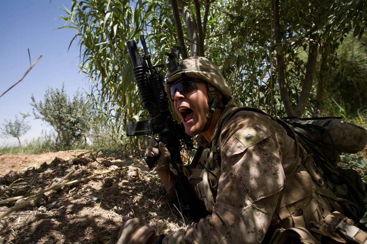 Marines of the first platoon of Lima company of the 3rd Battalion, 6th Marines, shouts out the location of Taliban shooting at his fire team in northern Marjah. The Marines took cover in canals and returned fire. The Taliban fled on motorbikes 15 minutes after shooting at the Marines. Four months after a major offensive to secure Marjah, the 3rd battalion, 6th Marines continue to face resistance as they attempt to win over the population in the rural area, which is a major poppy production center.