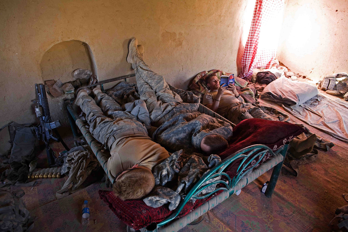 Sergeant Bryan Hulit, right, reads while fellow soldiers get some sleep on an Afghan bed they found in the compound they took over during their clearing operations in the village of Talukan. The 1st Battalion, 187th Infantry Regiment, Third Brigade Combat Team, of the 101st Airborne Division started to clear the roads and houses of the village of Talukan in Pajwai district of Kandahar. The soldiers have found as many as 9 Improvised Explosive Devices all around the main market and roads leading into the village.
