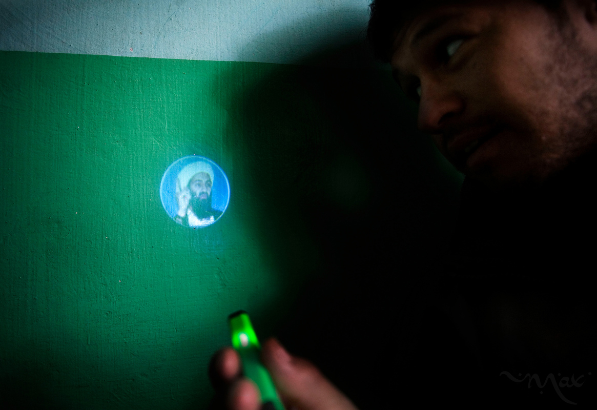 Burhan Amin, 26, shines a light from the back of a cigarette lighter that projects the image of Osama bin Laden that he purchased from a shop in the village of Khenj, Afghanistan on Friday, October 26, 2007. Ten years after the September 11th attack on the United States bin Laden was killed in Pakistan.