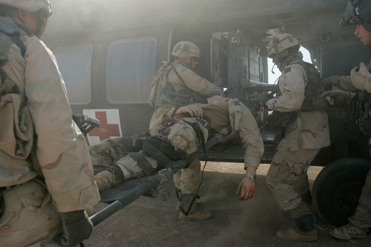 A gravely wounded U.S. soldier is loaded onto the helicopter for medical evacuation. Only one of the two reported wounded was at the landing zone as one soldier was driven to the nearby hospital. Suffering from two severed legs and an open stomach wound, medics on the ground applied two tourniquets to the wounded soldier on the scene where his vehicle was ambushed by a grenade attack.