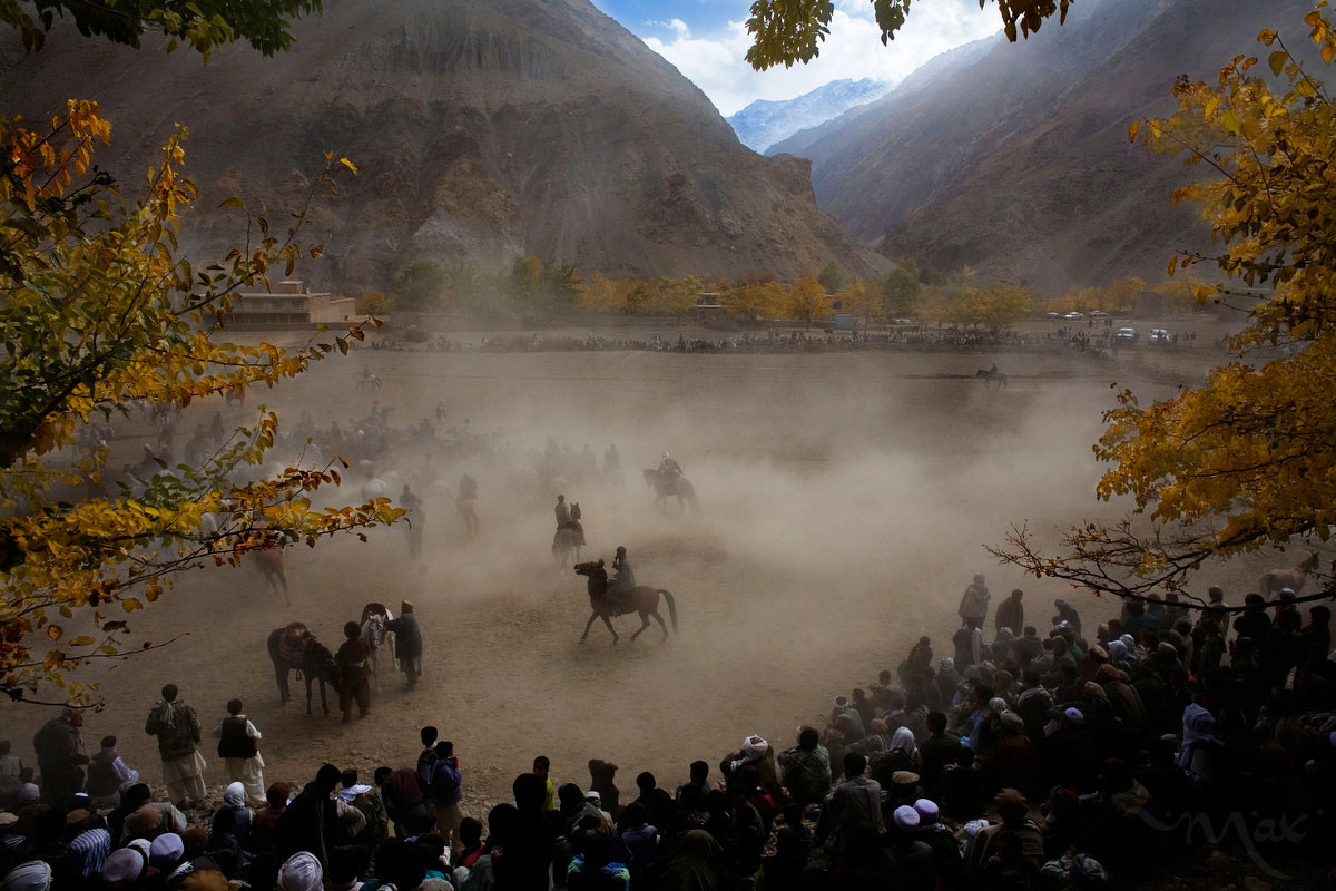 In a rare respite from the rigors of their work in the emerald mines in the mountains high over their village or from workshops and business, the men of Khenj, Afghanistan, compete in a game of Buzkashi on Friday, October 26, 2007. The popular game, banned under that Taliban, is a match between villagers on horseback pitted against each other to grab the carcass of a dead goat, or in this case, a dead calf, with its head cut off, from one location in the playing field, around a flag and set in a circle in another location. Each time a rider successfully completes the task he is cheered by the crowd gathered under the fall leaves in the shadow of the Hindu Kush.