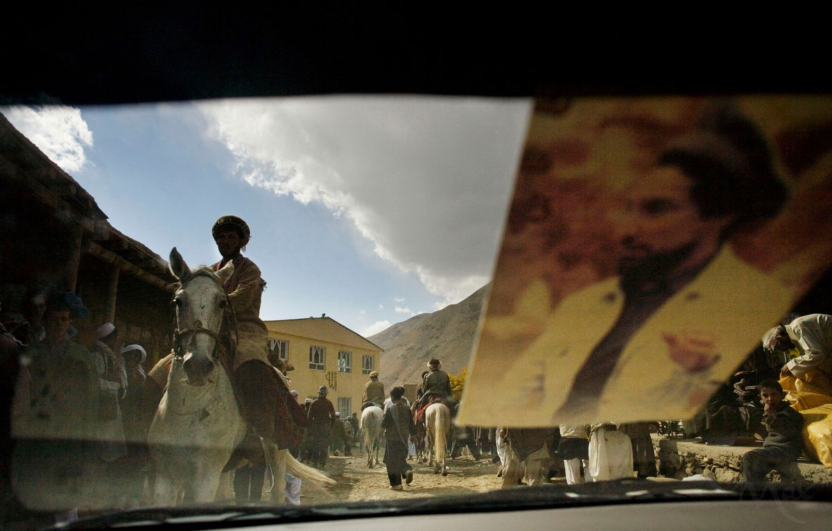 A car with a photo of the revered leader of the Panjshir resistance against the Russian invasion, Ahmed Shah Massoud, drives past horsemen after a buzkashi match in the village of Khenj, Afghanistan on October 26, 2007.