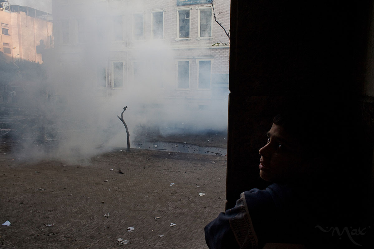 CAIRO, EGYPT. A boy hides behind a doorway after protestors fled advancing security forces who fired tear gas against protestors near the Interior Ministry in Cairo, Egypt on Saturday February 4, 2012. Protestors and police continued street clashes in the Egyptian capital following a deadly soccer riot that left 74 people dead and angered Egyptians over the lack of security.