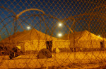 Detainees pray, as dawn breaks over the level-one detention area of Camp Redemption at the Abu Ghraib prison complex. The camp has level one to four detention levels with the level-one camp housing the best-behaved prisoners. This camp was built after the prisoner abuse scandal made the prison infamous. The U.S. released the buildings where the abuse took place to the control of the Iraqis and now runs its operations in this new camp.
