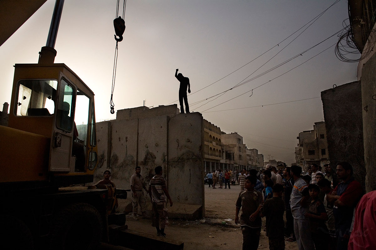 A crane worker stands on top of a blast wall while helping to move it to open al Kifah Street and the border between the Sunni and Shia parts of the Fadhil neighborhood of Baghdad. The Fadhil neighborhood was a center of sectarian and militia activity but security has improved in the neighborhood enough to take down the blast wall on the main street that is traditionally a shopping area for basic industrial goods. Members of the Sunni and Shiite Awakening councils, Iraqi military and U.S. Army came together after iftar, the meal breaking the fast during the month of Ramadan, to celebrate the event.