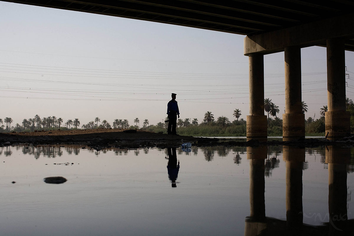 Iraqi Policeman Mohammad Nassir stands guard under one of the main bridges leading into the city of Nasiriyah over the Euphrates River. The bridges were key to attacking American forces in order to get their heavy tanks and armor over the river. Nassir was a child when the Americans first came in but he remembers seeing the Americans attacking several of the houses near the bridge on March 23, 2003. He now works as an Iraq Policeman guarding the bridge and watching for suicide bombers entering the city.