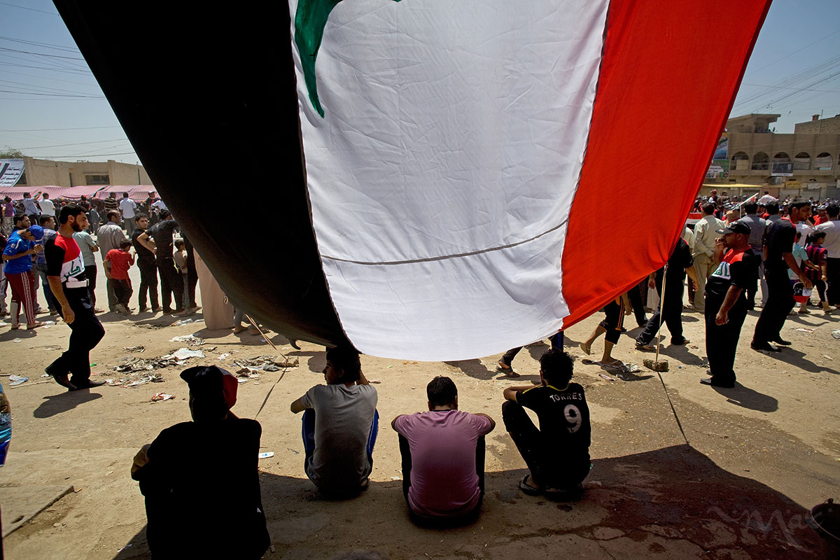People find protection from the 100-degree heat as they watch over 70,000 unarmed men loyal to the anti-American cleric Muqtada al-Sadr march in the Shiite neighborhood of Sadr City in eastern Baghdad, on Thursday May 26, 2011.