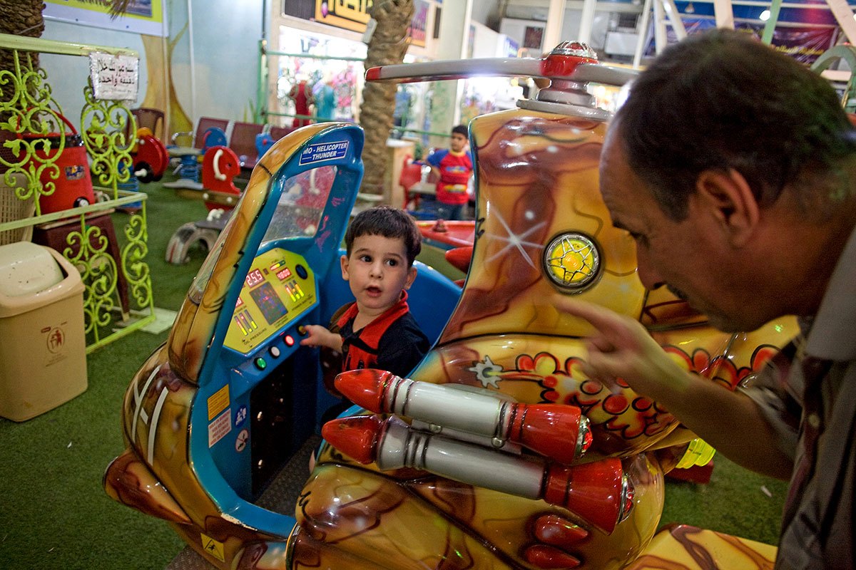 Mohammed Qusai, left, gets instructions from his father on how to operate the buttons on a coin operated helicopter ride at the tent market in downtown Basra, Iraq on August 21, 2010. Helicopters have been a constant reminder of war for Iraqis as Saddam Hussein used them under the treaty of the 1991 Gulf War and terrorized Shiite resistance fighters who rose up during the Gulf War thinking the Americans would overthrow Saddam. Since 2003 American and British helicopters have been the main transportation of foreign soldiers around the country because the roads proved too dangerous. The current Iraqi Air Force has around 150 helicopters and plans to buy American made F-16 fighter jets.