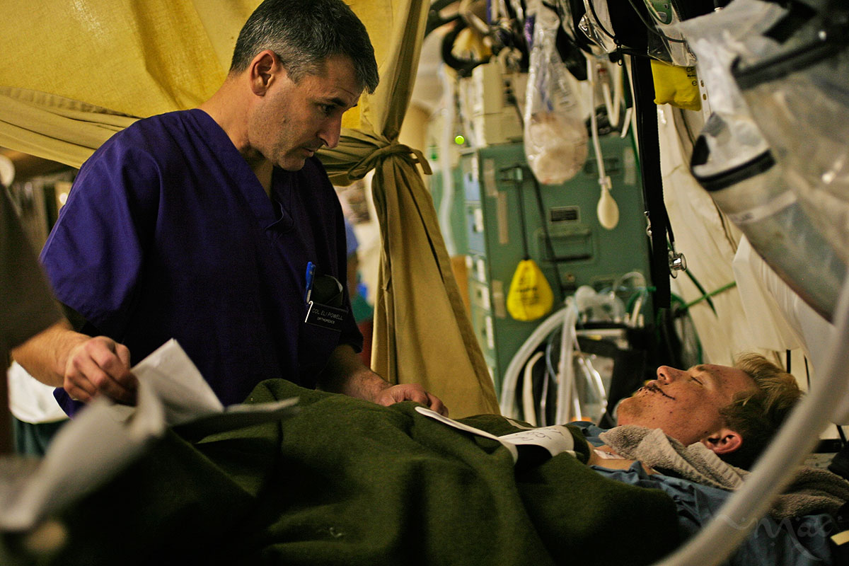 Commander of the 332nd Expeditionary Medical Group at the Air Force Theater Hospital in Balad, Iraq, Colonel Elisha Powell, left, gets information from a newly arrived wounded soldiers.