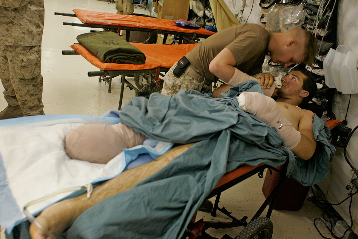 Corporal John Apollony, center, holds the hand of fellow Marine, Lance Corporal Matthew Schilling, after finding each other in the hospital in Balad on August 27, 2005. Corporal Apollony, who was in the hospital for a fractured hand, heard Schilling was injured in an improvised explosive device attack in Hit, Iraq the day before.