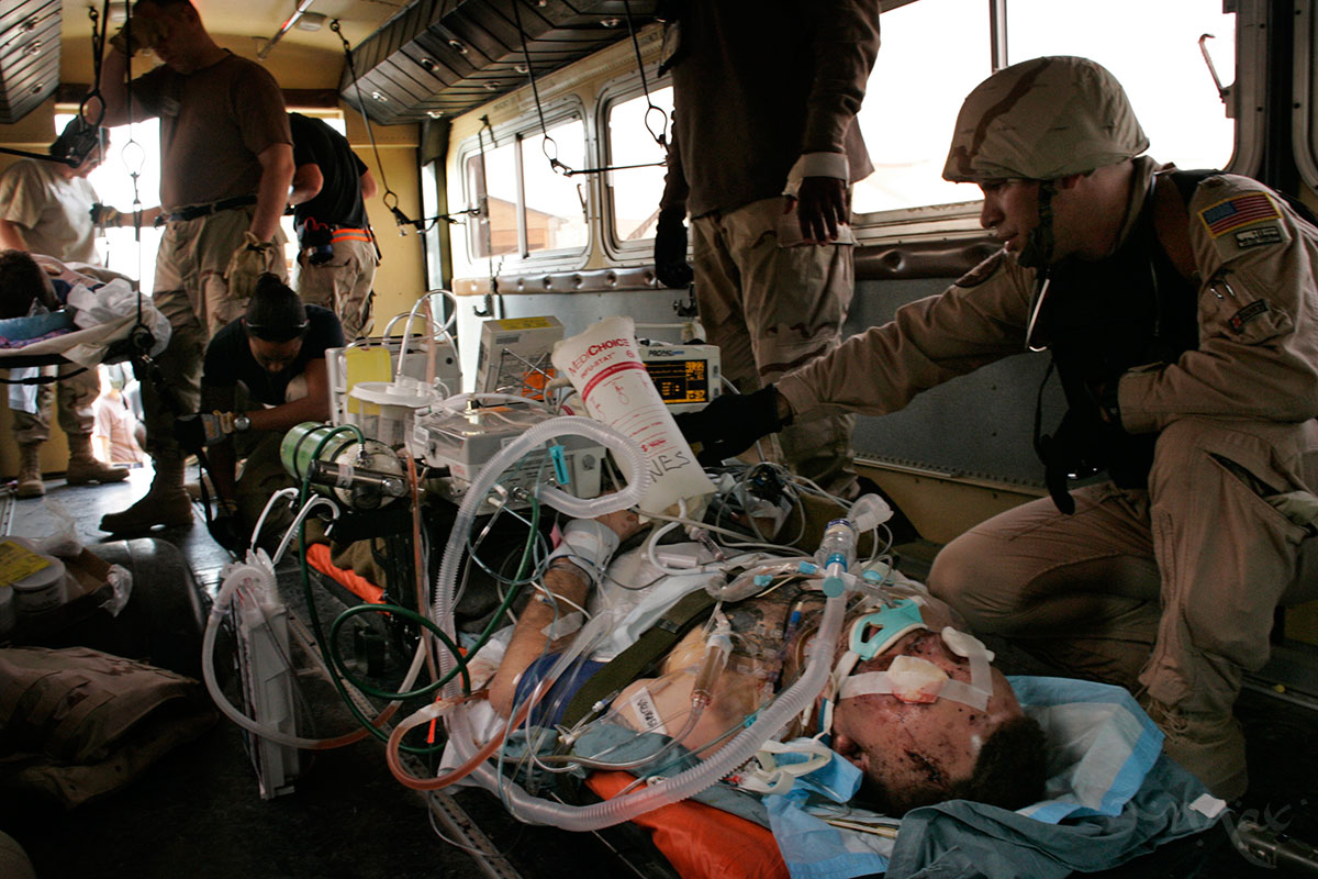 Tech Sergeant Darrell Waite, right, with the Critical Care Aeromedical Team (CCAT) transport a critically wounded Marine from the Balad Theater Medical Hospital in Balad, Iraq to a waiting aircraft ready to fly to Landstuhl, Germany.