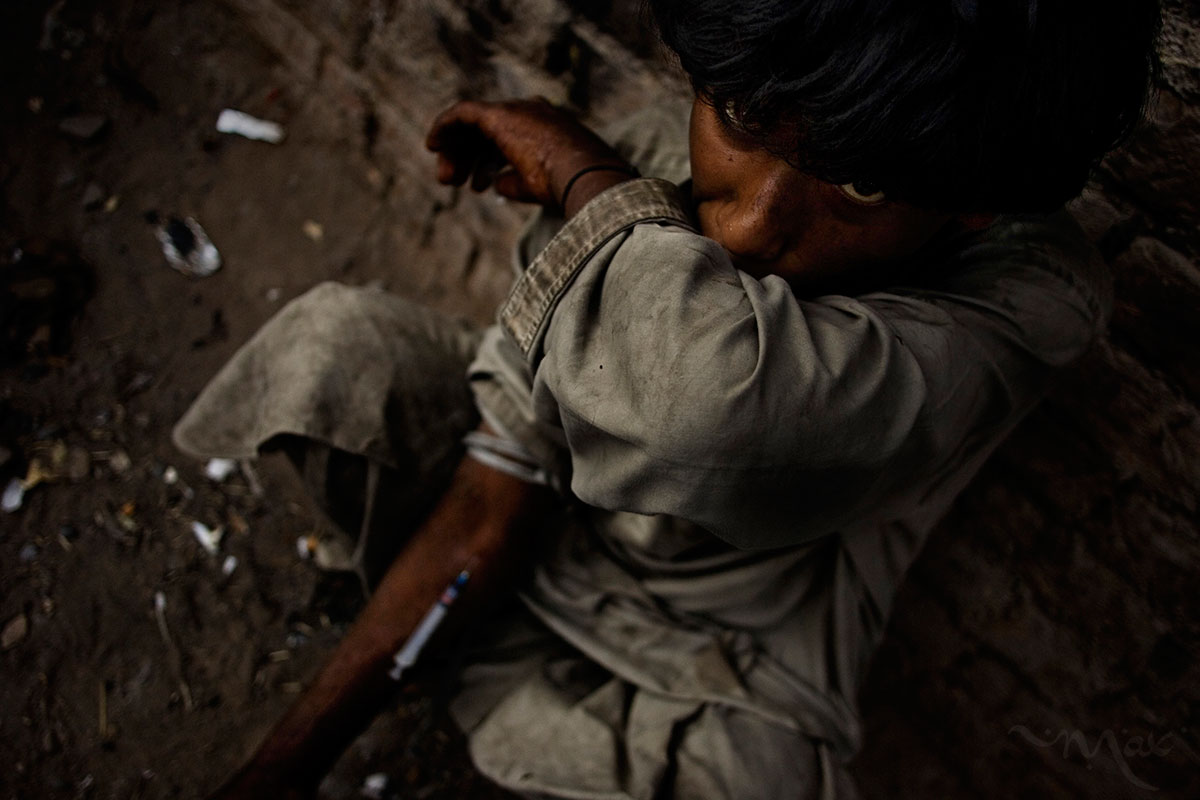 PESHAWAR, PAKISTAN. After taking a hit of heroin an addict wipes his face in a back alley on the streets of Peshawar, Pakistan on Sunday March 2, 2008. Record poppy crops in Afghanistan have pushed a surge in heroin addicts across the border in Pakistan. The use of intravenous injection of the drug is helping to spread HIV/AIDS in areas where there is little or no help for those with the disease.