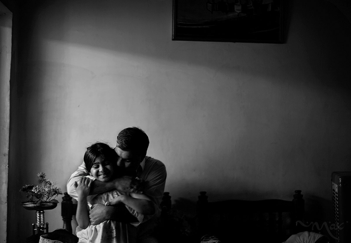 BAGHDAD, IRAQ. Mohammad Raheem embraces his daughter and is momentarily relieved of the pain as he retells his experience in that very room four years ago to the day on Haifa Street in Baghdad, Iraq on Tuesday September 12, 2008. In 2004, a massive explosion shattered the windows of his home sending shards of glass flying through the room where he slept on the floor with his wife and three children between them. Mohammad's face was cut by glass and so were the legs of his small daughter. The explosion was a car bomb targeting an American patrol, wounding soldiers in an U.S. tank and wounding Mohammad's family. The improvement of security in Iraq during 2008 and the passing of time is slow to remove the emotional scars left after the burning tank was pulled away, the dead buried and the windows repaired.