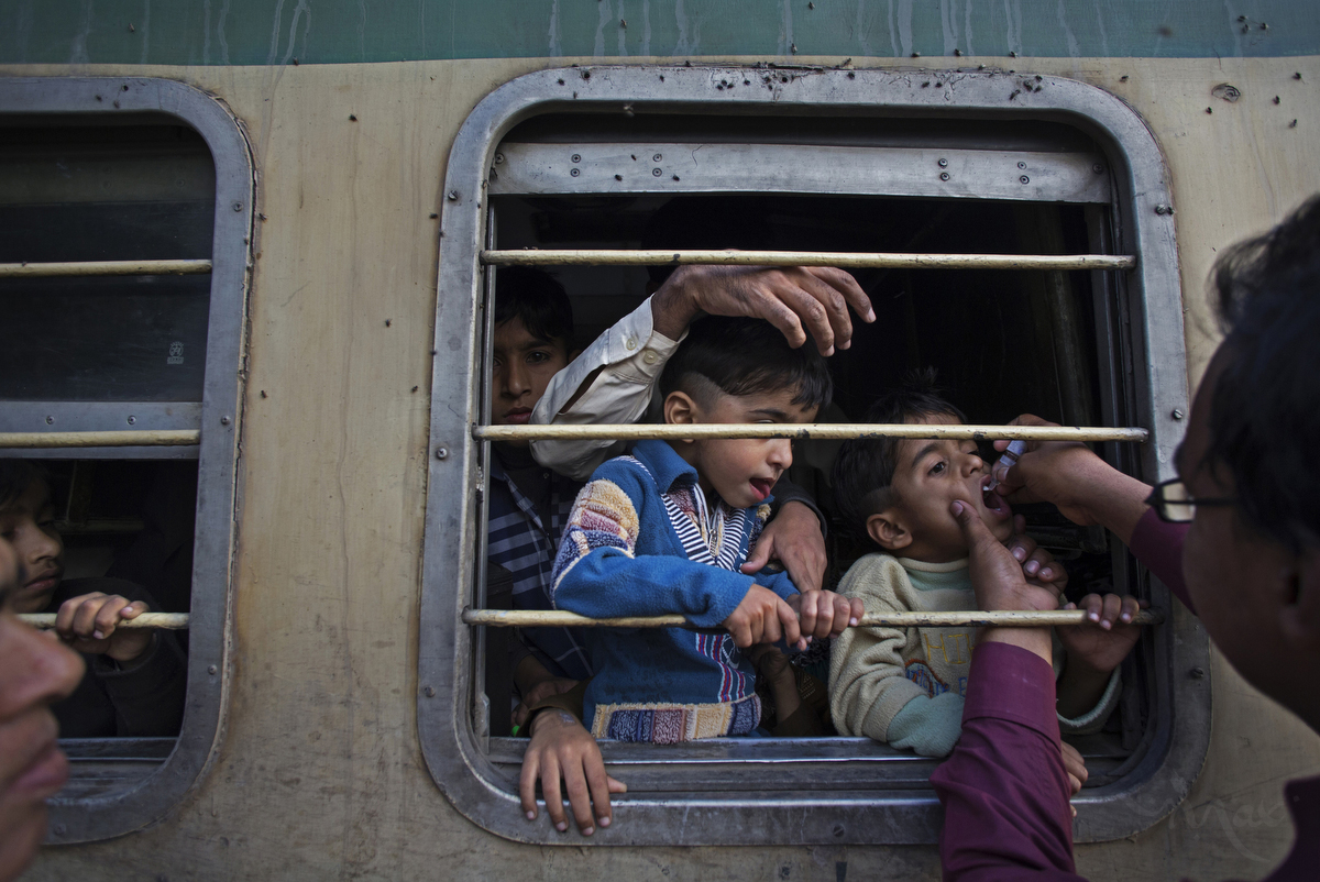 KARACHI, PAKISTAN. A government team administers Polio immunization drops to children between the ages of 0 to 5 at the Karachi train station in Karachi, Pakistan on Thursday January 30, 2014. The three-day campaign was cut short after an immunization team was attacked and two workers killed the following day. Pakistan remains one of the most difficult polio eradication environments with the death toll among anti-polio workers reaching 65 since the first targeted attack in December of 2012.