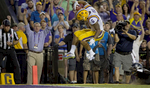 LSU running back Derrius Guice (5) leaps into the end zone in front of Missouri safety Thomas Wilson (8) during the first half of an NCAA college football game in Baton Rouge, La., Saturday, Oct. 1, 2016. (AP Photo/Max Becherer)