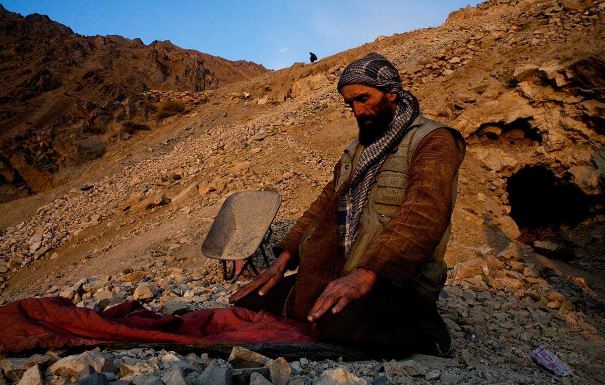 Moulana Latife, 45, prays on an outstretched jacket at the mouth of his mine in the mountains overlooking the Panjshir Valley village of Khenj, Afghanistan on Thursday October 25, 2007. Latife has been working in the mines since he was 16 and fought with Ahmed Shah Massoud against the Russians in the 1980s and the Taliban after that. Most of the men at the times are deeply independent and conservative and trying to make a living from the back breaking work.