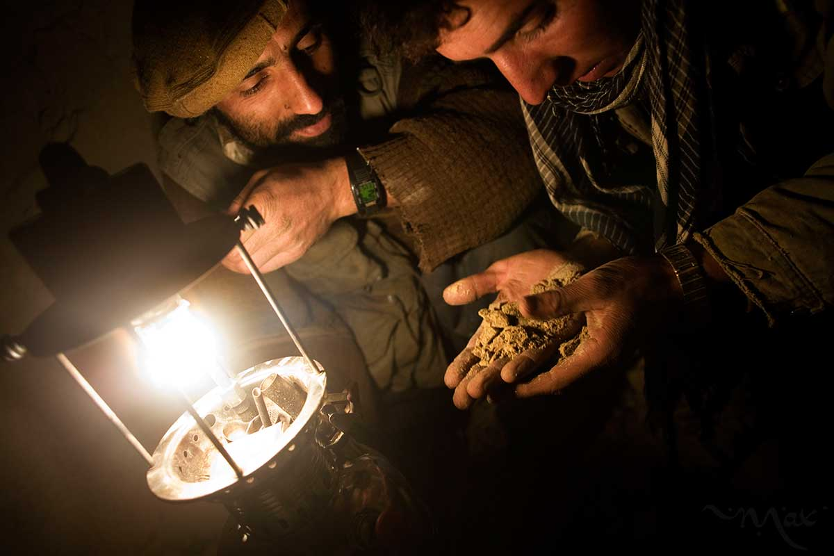 Ahmad Lais Amin, 22, right, looks for signs of emerald in a handful of dirt he has excavated as, Aziz, a miner from a nearby cave holds the light and looks for signs of success in the slope of the Hindu Kush mountains towering over the Panjshir Valley near the village of Khenj, in Afghanistan on Thursday October 25, 2007. Miners sometimes drop in on promising excavations to snoop for better locations or to watch a big find.