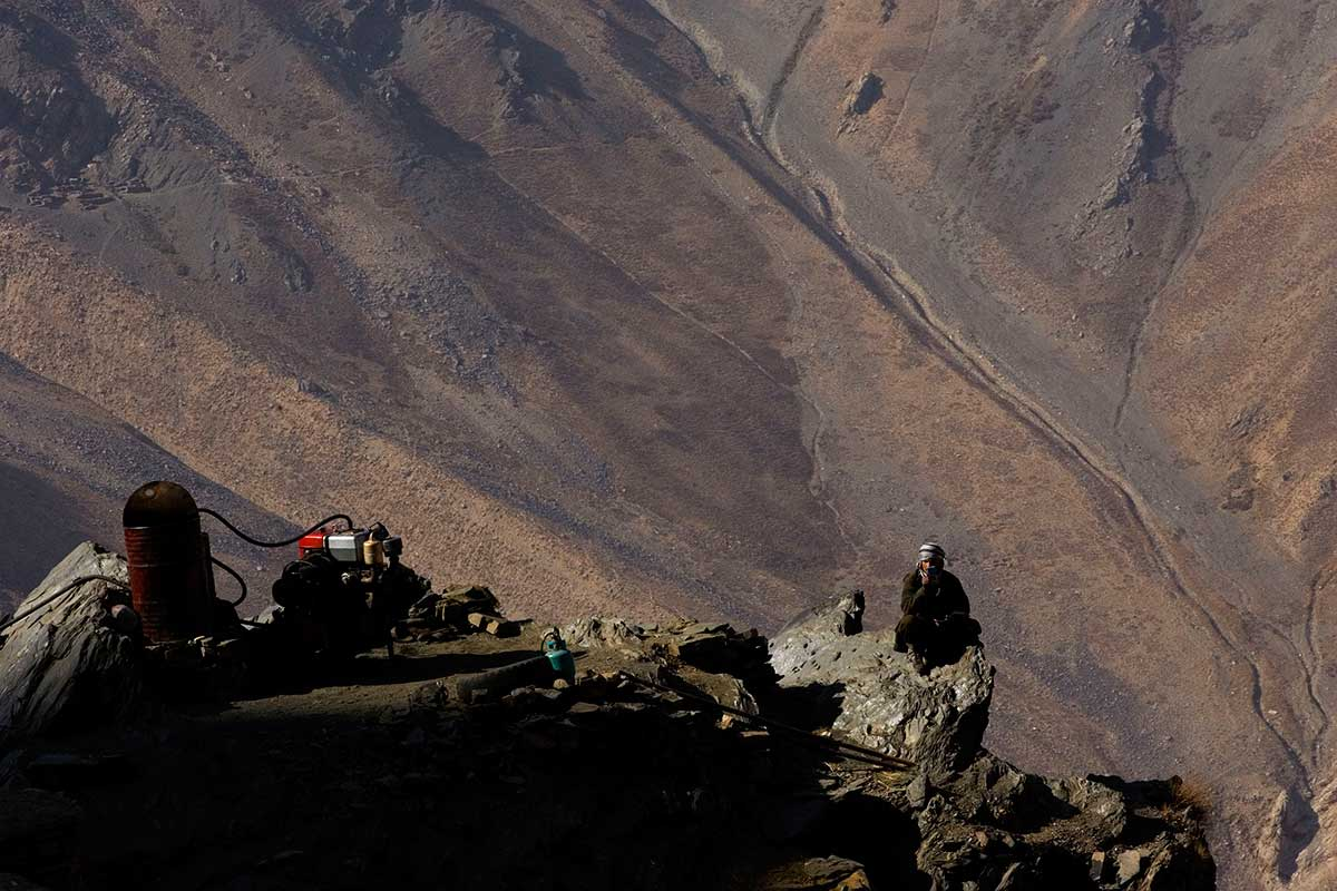 An emerald worker is perched on a rock next to his generator and compressor that operate his air pressure driven rock drill as the morning sun creeps over the Western face of the mountain above the Panjshir Valley village of Khenj, Afghanistan on Wednesday, October 24, 2007. The river of mine tailings can been seen in the mountain in the background. The miners' work is of environmental concern and the miners often also extract and dump valuable metals that exist around the emerald according to Mohamad Ibrahim, the Minister of the Mines and Industry Ministry in Kabul.