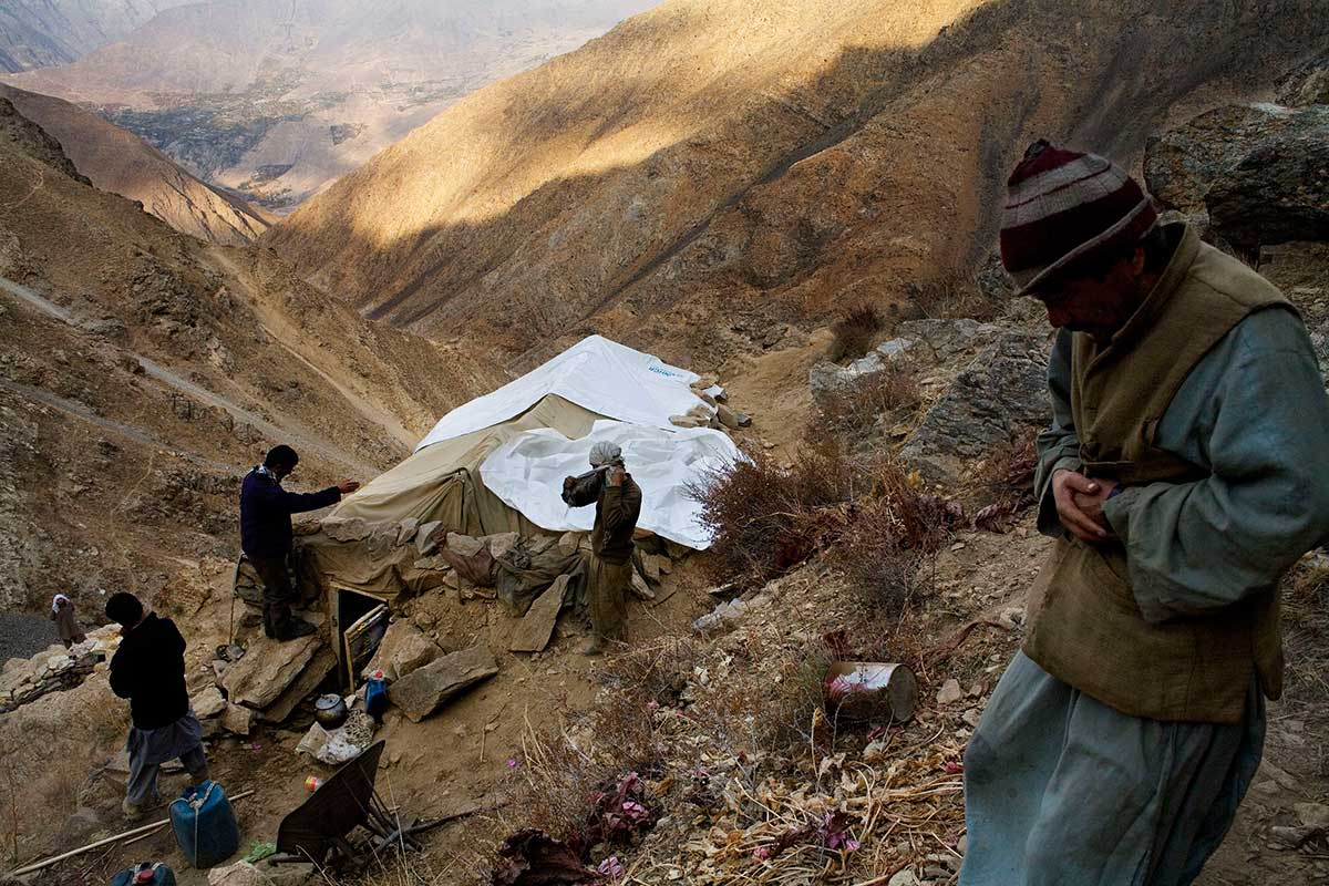 With the Panjshir Valley village of Khenj visible thousands of feet below, emerald miners reinforce the roof of their mountainside tent home in Panjshir province, Afghanistan on Wednesday, October 24, 2007. The miners haul water from an abandoned mine that now is full of spring water but have to haul all other provisions from the village below. Gas stoves heat water for washing and gas lamps provide light for the mines and tents. Generators are reserved to operate jack hammers and air compressors for mining drills.