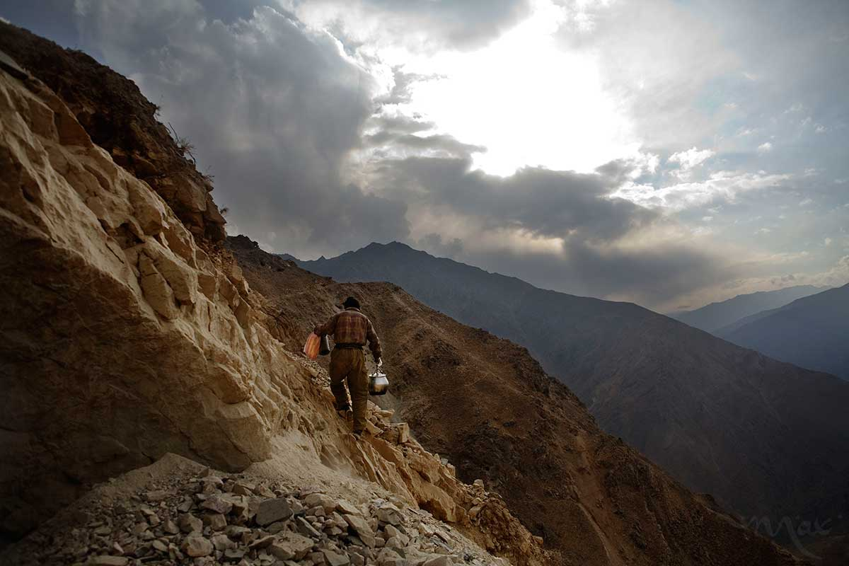 Having delivered a lunch of rice and lamb meat, Rahimullah, 27, scales the sheer rock face back to the stone cabin where he will clean up the pots and pans from the meal before returning to continue mining on mountains over the Panjshir Valley village of Khenj, Afghanistan on Wednesday, October 24, 2007.