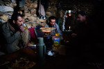 Ahmad Jawead, 22, left, Rahimullah, 27, center, and Burhan Amin, 26, right, share a breakfast of cream, bread, jam and tea as they make the day's bread on a gas burner in their stone one-room home in the mountains next to the mine they work above the Panjshir Valley village of Khenj, Afghanistan on Wednesday, October 24, 2007.  Ahmad Jawead and Burhan Amin are cousins and hire Rahimullah to help with the work of the mines. Teams of five to ten men, sometimes friends or family, work as partners in the mines.