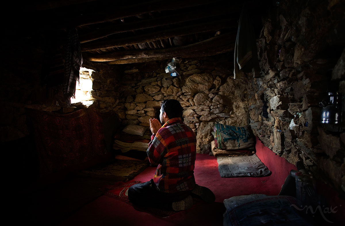 "Burhan Amin, 26, prays in the one-room stone house he shares with the rest of his team of miners on the slopes of the Hindu Kush mountains towering over the Panjshir Valley near the village of Khenj, in Afghanistan on Thursday October 25, 2007. Amin, 26, has a kidney ailment that does not allow him to work, brought on from years of battling the mountain for emeralds. Instead of manning the rock drill, Amin prepares the meals of rice, bread, lamb meat and tea for grime-covered miners.  Even with this light duty, he sometimes feels too ill to work. 	""Most of the time I am sick. Those days when I am not feeling well, because there is the mountain and it is the work of the mountain. If we work from the morning till night, you will know how much you get tired,"" Amin said."