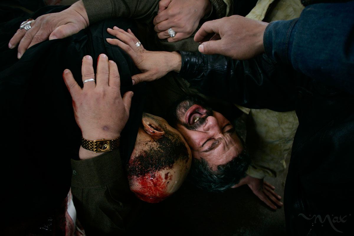 With hands of family members reaching out to him, Karim Rahim Judi Yacoubi, bottom right, shouts out in grief as he holds the corpse of his brother, Naim, 37, who was killed during a suicide bombing during Election Day in Baghdad. Naim was killed while he was taking tea to election officials at an Iskin neighborhood polling station where he had voted earlier that day. Naim's body was being prepared for burial in the Najaf cemetery washroom when the family mobbed the body in an outpouring of grief.