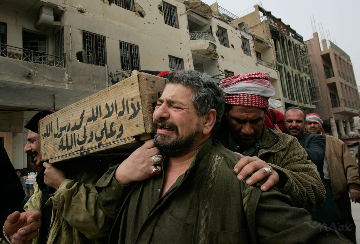 Karim Rahim Judi Yacoubi, center, weeps as he and his brothers carry the corpse of their dead brother, Naim, 37, to be blessed at the Imam Ali shrine in Najaf before burial. Naim was killed while he was taking tea to election officials at an Iskin neighborhood polling station where he had voted earlier that day.