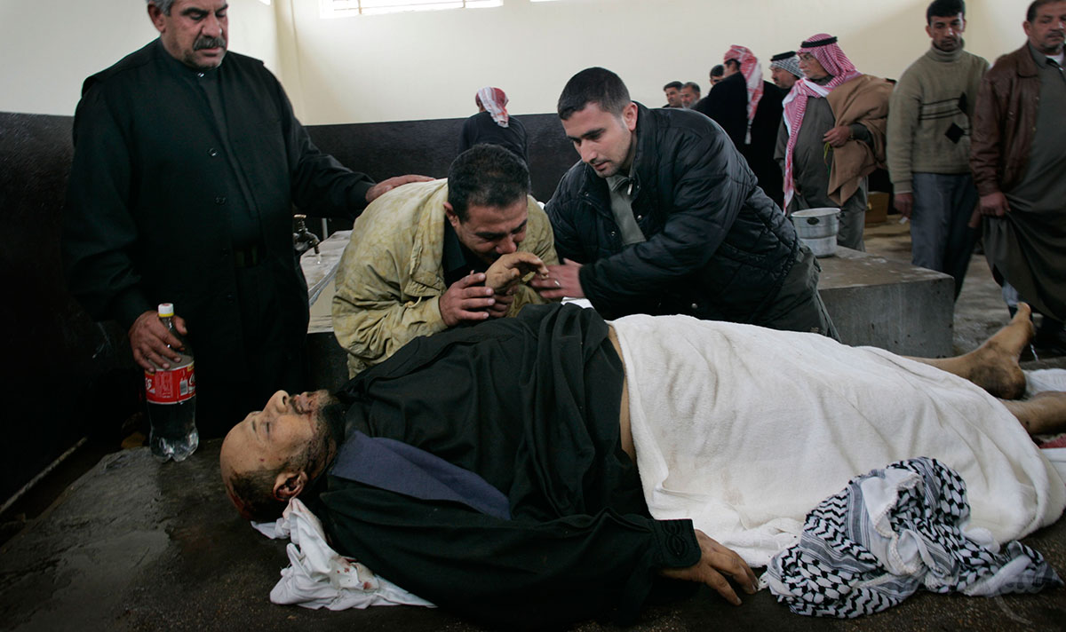 Salim Rahim Judi Yacoubi, gently kisses the hand of the corpse of his brother, Naim, 37, who was killed during a suicide bombing on Election Day in Baghdad. Naim was killed while he was taking tea to election officials at an Iskin neighborhood polling station where he had voted earlier that day.