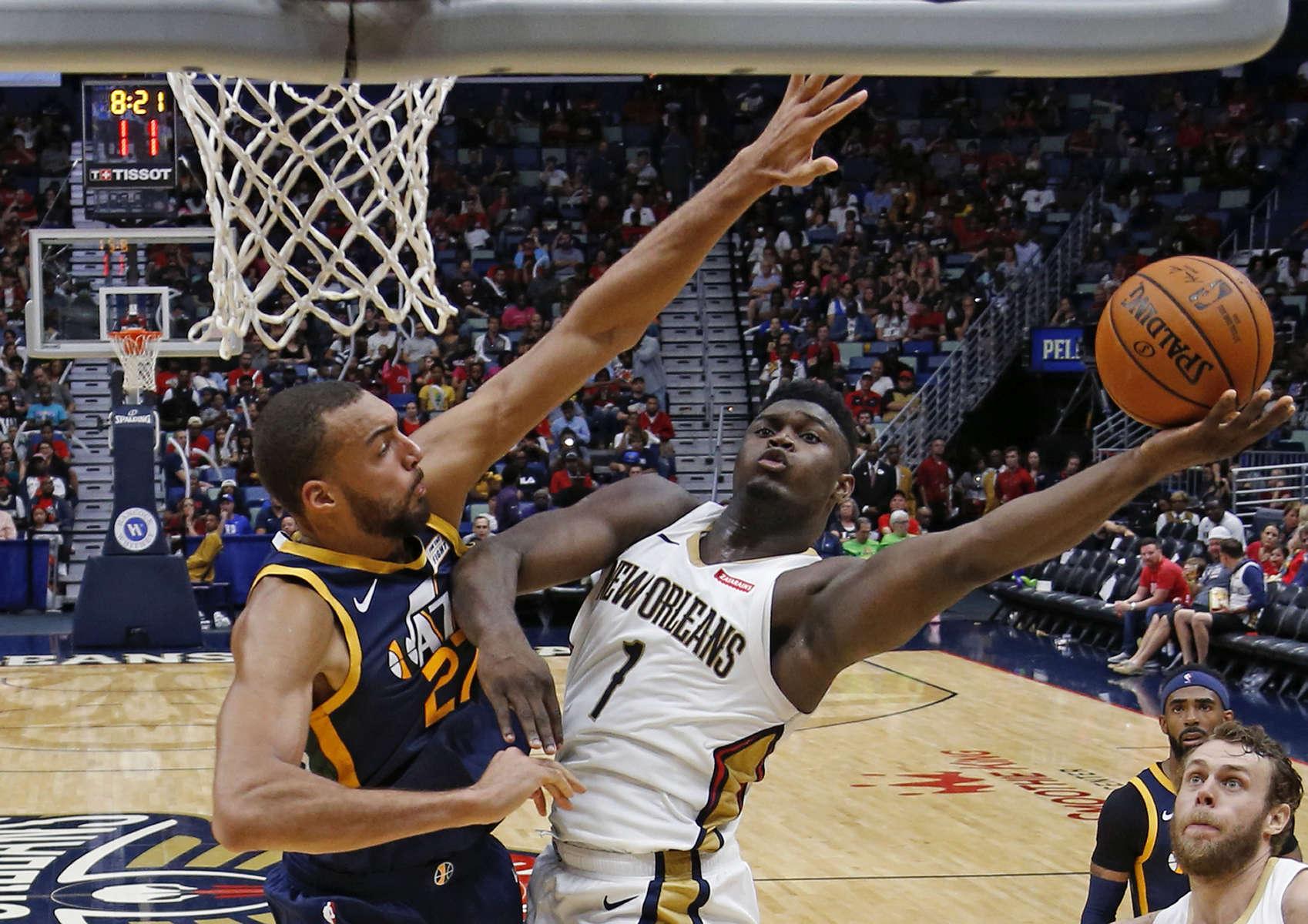New Orleans Pelicans forward Zion Williamson (1) makes a layup against Utah Jazz center Rudy Gobert (27) during the second half an NBA preseason basketball game in New Orleans, Friday, Oct. 11, 2019. The Pelicans won 128-127.