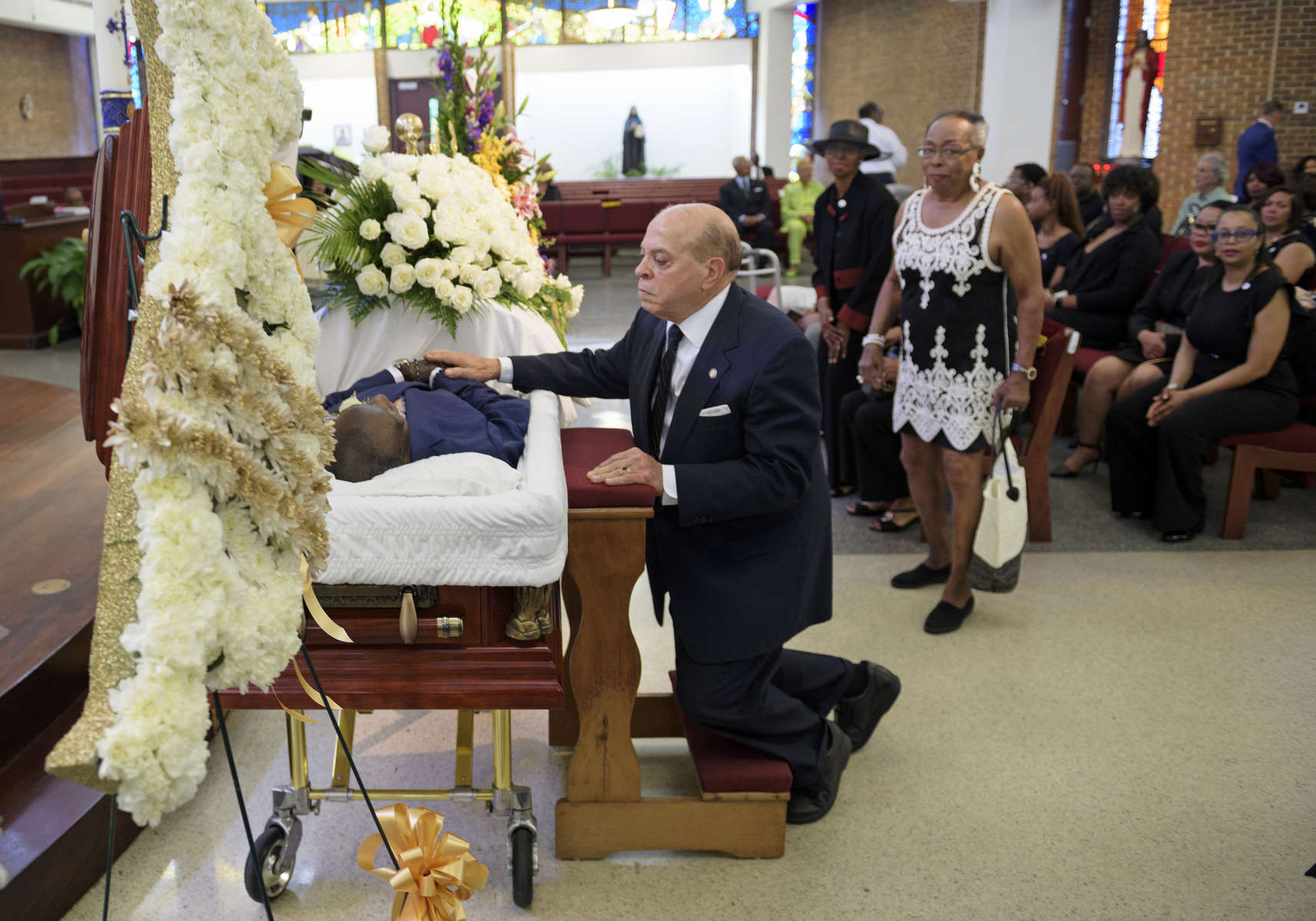 Deacon John Moore touches his friend for the last time during the viewing of Dave Bartholomew at St. Gabriel the Archangel Church in New Orleans, La. Monday, July 8, 2019. The life of David Bartholomew, a trumpeter, bandleader, producer, arranger, composer and star-maker of Fats Domino, Lloyd Price and many other New Orleans talents, was celebrated with prayers, tributes, brass bands and dancing. He died at 100 years of age on June 23.