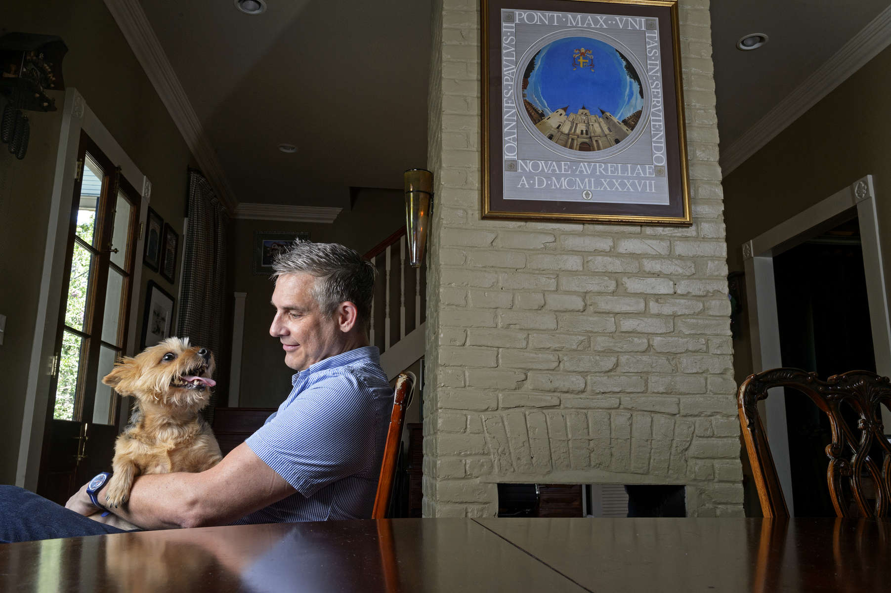 Kevin Bourgeois sits with his Norwich Terrier, Pippa, with a framed poster, from the papal visit of Pope John Paul II to New Orleans from 1987, seen behind him at his home in New Orleans, La. Tuesday, Aug. 6, 2019.