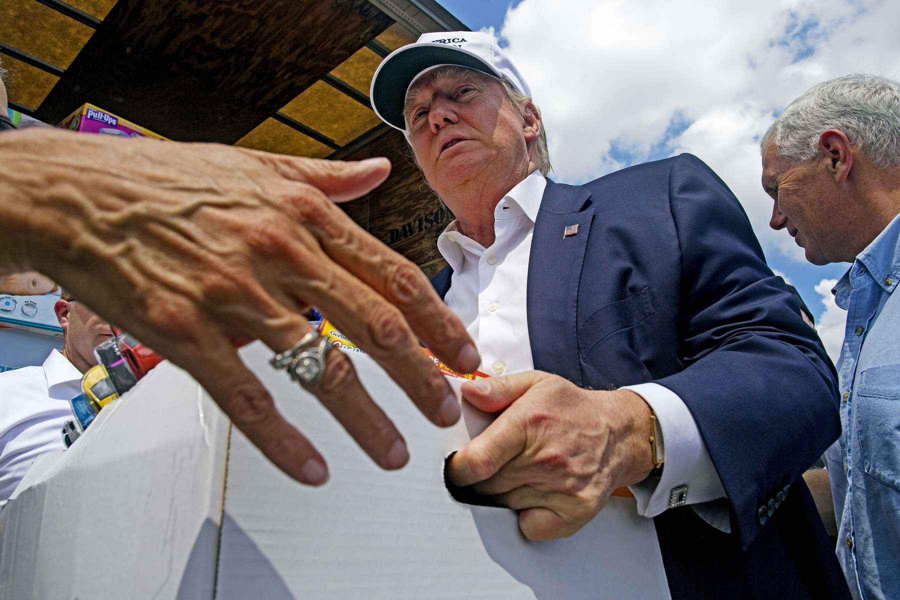 GONZALES, LOUISIANA. Republican presidential candidate Donald Trump, center, and running mate Gov. Mike Pence, right, help to unload supplies for flood victims during a tour of the flood damaged area in Gonzales, La., Friday, Aug. 19, 2016. Trump and Pence traveled to flood-ravaged sections of southern Louisiana to survey the damage that killed at least 13 people and displaced thousands more. (AP Photo/Max Becherer)