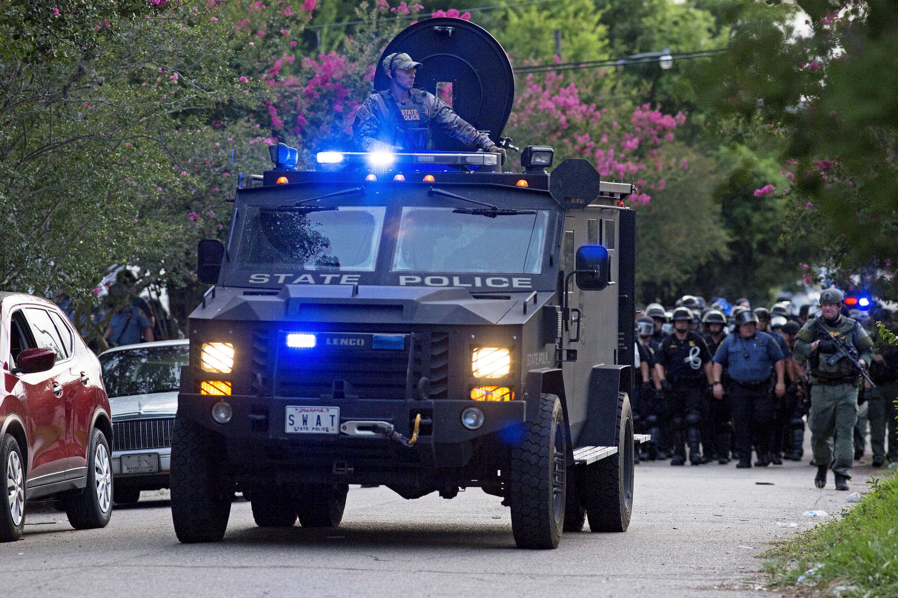 An armored police truck leads a troop of police through a residential neighborhood near a major highway  after clearing protestors from the area in Baton Rouge, La. USA, on Sunday, July 10, 2016. Some 30 to 40 people were taken into custody for trying to block a highway, sheriff's spokeswoman Casey Rayborn Hicks said. Louisiana Gov. John Bel Edwards said he doesn't believe officers have been overly aggressive by using riot gear to push protesters off a highway. {quote}The police tactics in response have been very moderate. I'm very proud of that,{quote} said Edwards (AP Photo/Max Becherer)