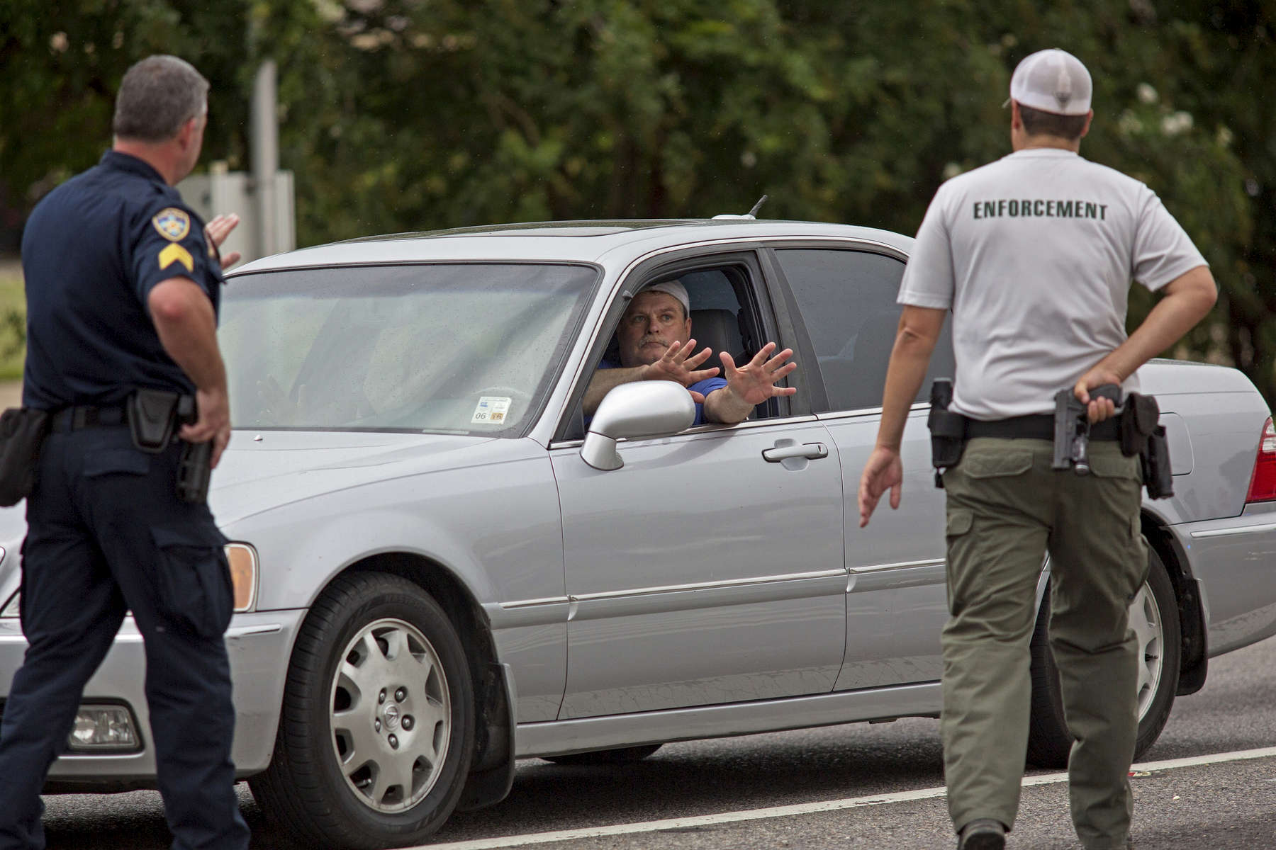 Police stop a car and direct the driver to show his hands after coming from the direction of a police shooting on Airline Highway in Baton Rouge, La. USA, on Sunday, July 17, 2016. The driver's car was searched, his identification checked, then he was allowed to continue. Three officers are confirmed dead and three others wounded after a shooting in Baton Rouge, Casey Rayborn Hicks, a spokeswoman for the East Baton Rouge Sheriff's Office said. (AP Photo/Max Becherer)
