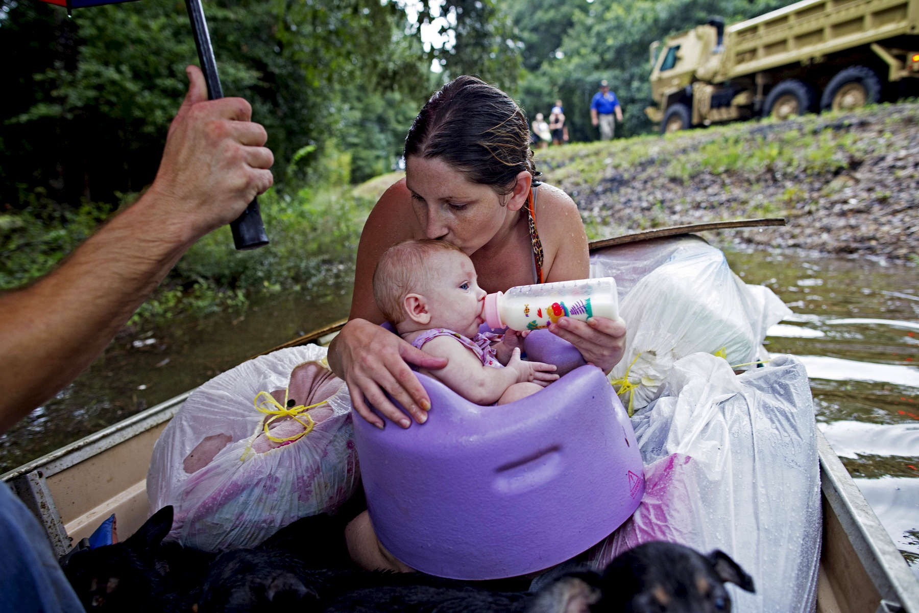 Danielle Blount kisses her 3-month-old baby Ember and feeds her while they wait to be evacuated by members of the Louisiana Army National Guard near Walker, La. USA, after heavy rains inundated the region, Sunday, Aug. 14, 2016. Downpours in some areas of southern Louisiana came close to 2 feet over a 48-hour period according to the National Weather Service. (AP Photo/Max Becherer)